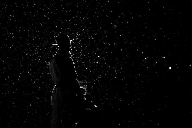 Dramática silueta de un hombre peligroso con un sombrero por la noche bajo la lluvia en la ciudad en el antiguo estilo crimen noir