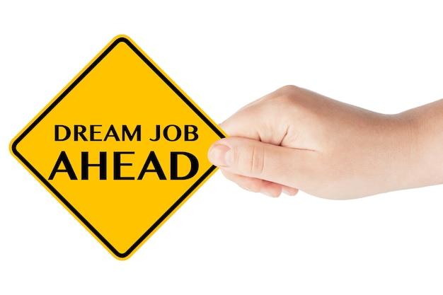 Dream job ahead señal de tráfico en la mano de la mujer sobre un fondo blanco.
