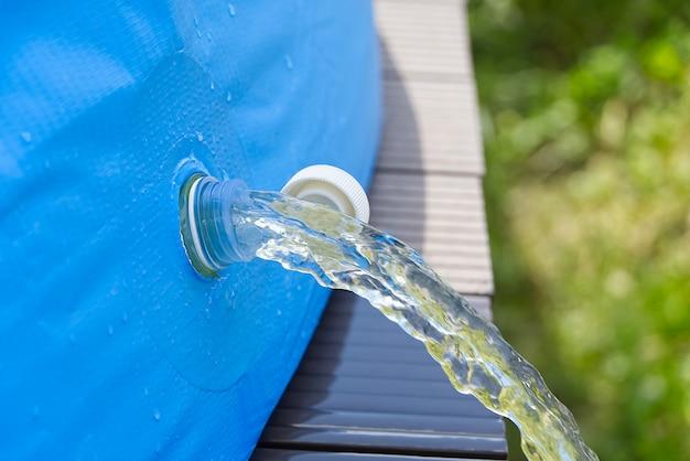 Drenaje de agua de una piscina inflable al aire libre. concepto de cuidado de piscina inflable.
