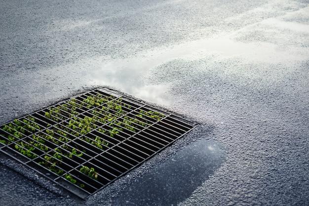 Drenaje de rejilla metálica vieja de alcantarillado en la calle después de una fuerte lluvia.