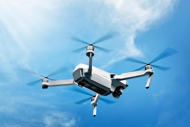 Drone blanco con cámara volando en el aire