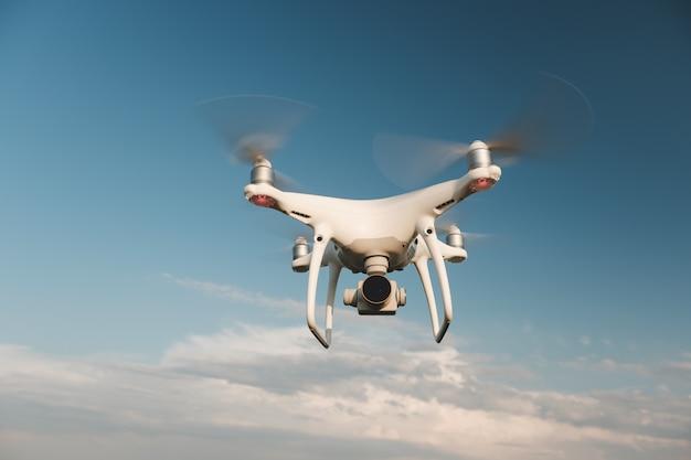 Drone blanco flotando en un cielo azul brillante