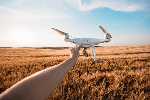 El drone blanco en manos del hombre.