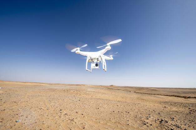 Drone blanco volando sobre una zona desértica reseca contra un cielo azul