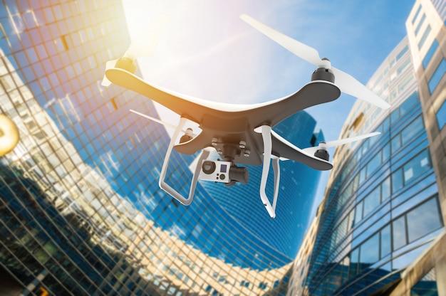 Drone con cámara digital volando en una ciudad moderna al atardecer