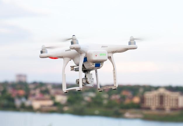 Drone quad copter con cámara digital de alta resolución volando sobre la ciudad