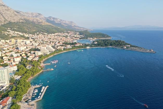 Drone vista de la ciudad de makarska rodeada por el mar bajo un cielo azul y la luz del sol en croacia
