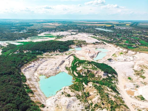 Drone vista sobre una cantera de caolín inundada con agua turquesa y orilla blanca