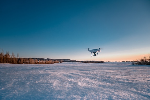 Drone volando por encima del campo cubierto de nieve en un día soleado de invierno
