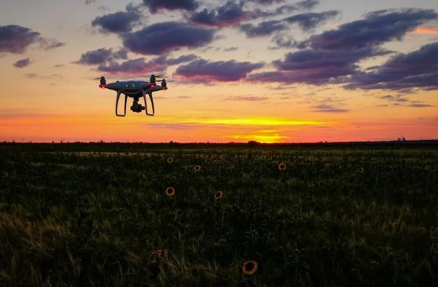 Drone vuela sobre el campo al amanecer. fondo tecnológico moderno - silueta de la máquina voladora en el cielo del atardecer rojo brillante.