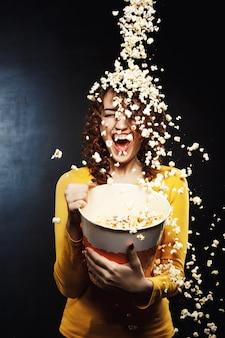 Ducha de palomitas de maíz. chica divirtiéndose con amigos, arrojando palomitas de maíz