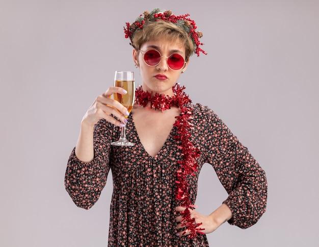 Dudosa joven bonita con corona de navidad y guirnalda de oropel alrededor del cuello con gafas sosteniendo y mirando una copa de champán manteniendo la mano en la cintura aislada sobre fondo blanco