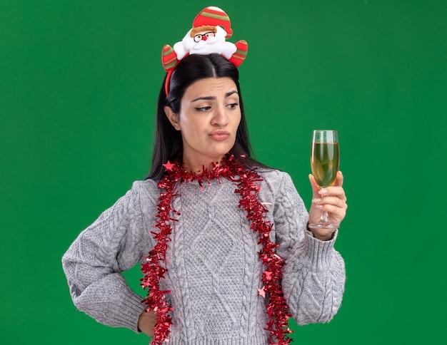 Dudosa joven caucásica con diadema de santa claus y guirnalda de oropel alrededor del cuello manteniendo la mano en la cintura sosteniendo y mirando una copa de champán aislado sobre fondo verde