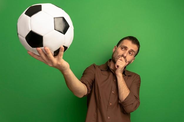Dudoso joven caucásico estirando el balón de fútbol hacia la cámara mirándolo poniendo la mano en el mentón aislado sobre fondo verde con espacio de copia