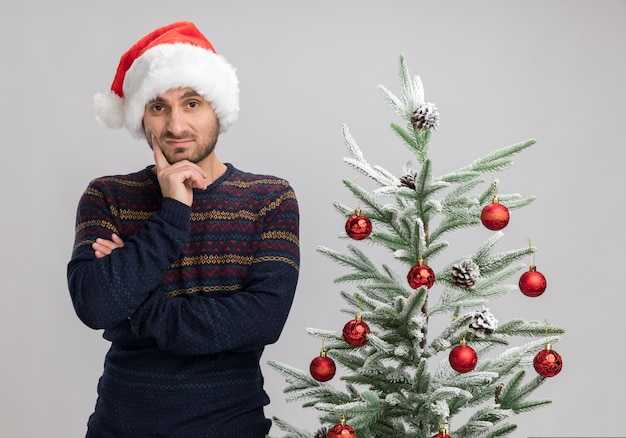 Dudoso joven caucásico con sombrero de navidad de pie cerca del árbol de navidad mirando a la cámara manteniendo la mano en el mentón aislado sobre fondo blanco.