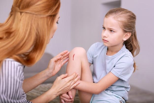 Duele. triste niña triste mirando a su madre mientras le muestra