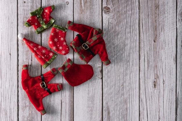 Duendes de navidad y ropa de santa claus sobre fondo de madera. copie el espacio. enfoque selectivo.