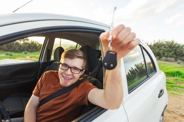 Dueño de auto feliz está mostrando la llave dentro de su auto nuevo.