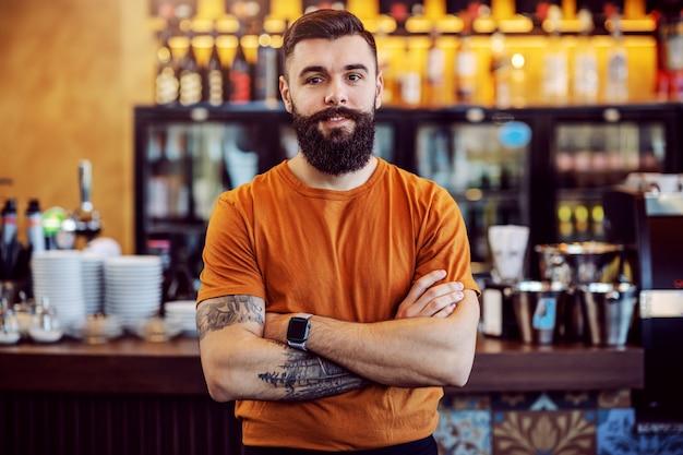 Dueño de café tatuado barbudo guapo joven de pie con los brazos cruzados