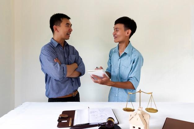 Dueño de una casa feliz hable con el abogado sobre la ley de vivienda.