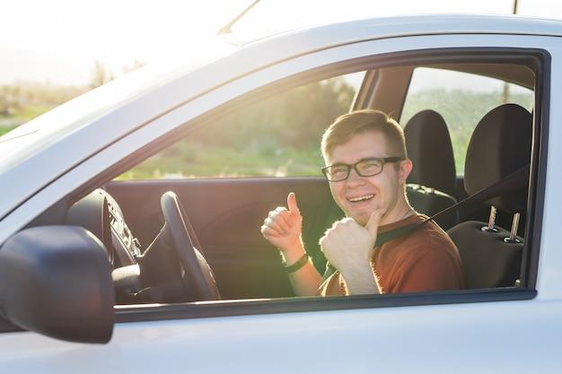El dueño del coche feliz está mostrando los pulgares hacia arriba dentro de su nuevo coche.