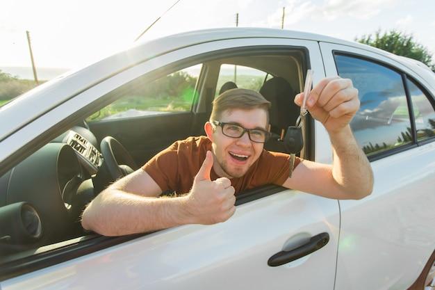 Dueño de coche feliz está mostrando los pulgares hacia arriba y su nueva llave de coche.