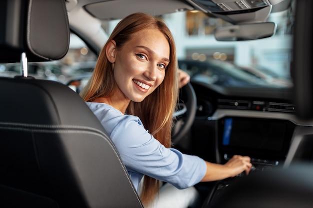 Dueño de coche nuevo mujer feliz sentado en el asiento del conductor y mirando a su alrededor