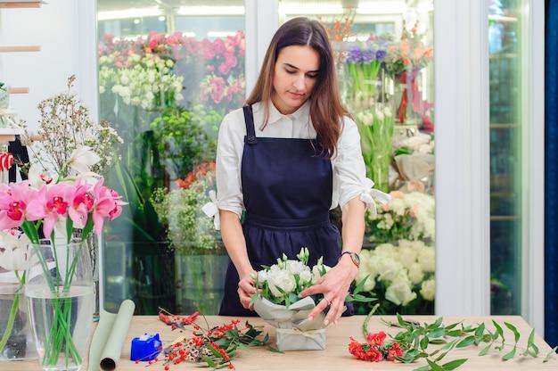 El dueño de una florería hace un ramo de rosas blancas.