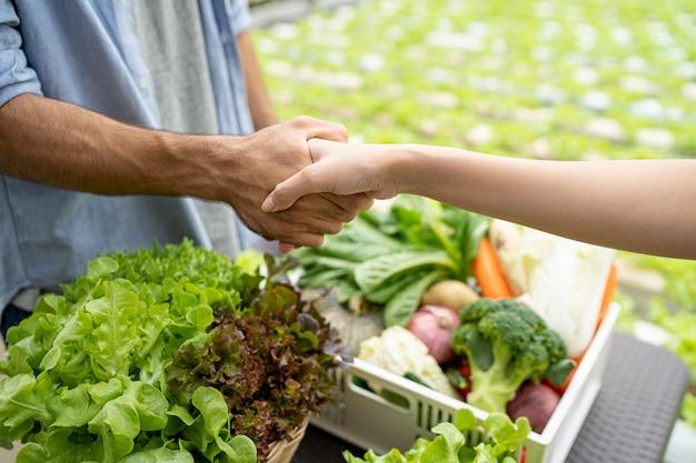 El dueño de una granja de vegetales orgánicos habló con los clientes sobre el negocio de exportación. dar la mano al hablar con éxito.