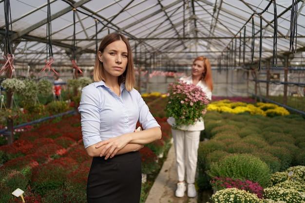 Dueño de invernadero sonriente posando con los brazos cruzados con muchas flores y un colega sosteniendo una olla con crisantemos rosados bajo techo de vidrio
