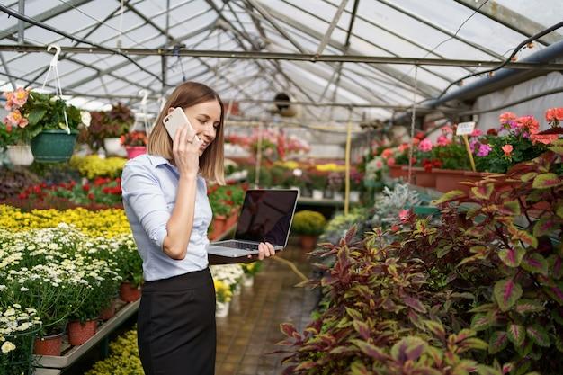 Dueño de invernadero sonriente posando con una computadora portátil en sus manos hablando por teléfono con muchas flores y techo de cristal.