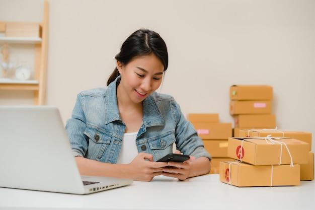Dueño joven asiático elegante hermoso de la mujer de negocios del empresario de la pyme que comprueba el producto en el código común del qr de la exploración que trabaja en casa.