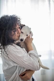 Dueño de mascota mujer morena rizada feliz celebración de perro jack russell terrier raza sentimiento amor amistad