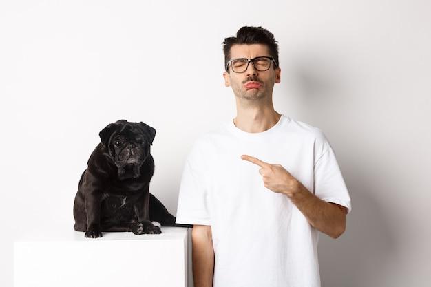 Dueño de mascota triste y sombrío apuntando a su perro pug negro y sollozando, de pie upster contra el fondo blanco.