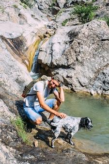 Dueño masculino de perro spaniel caminando contra las montañas y el fondo de la cascada