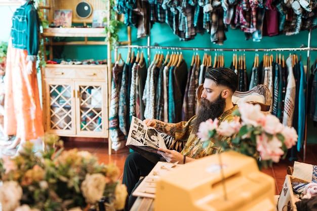 Dueño masculino de la tienda que se sienta en silla en su tienda de ropa
