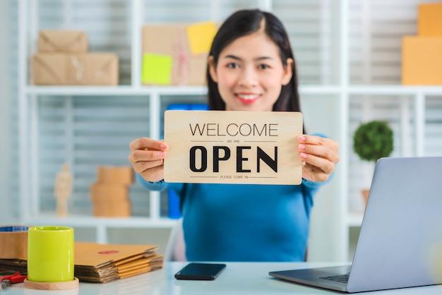 Dueño de negocio asiático joven de la mujer que lleva a cabo la muestra abierta