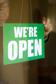 Dueño de un negocio colgando un cartel abierto en una puerta de vidrio