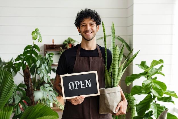 Dueño de negocio feliz sosteniendo estamos abiertos signo