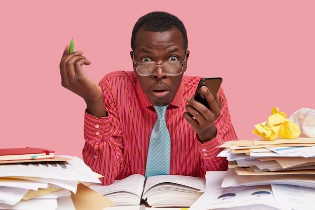 El dueño de un negocio masculino negro confundido sostiene el teléfono móvil en una mano, el bolígrafo en la otra, mantiene la boca abierta, se viste formalmente, hace el pago a través de una aplicación especial