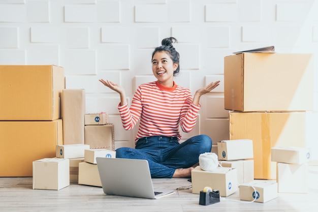 Dueño de negocio de mujeres asiáticas que trabaja en casa con caja de embalaje en lugar de trabajo
