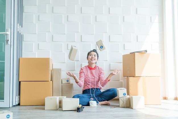 Dueño de un negocio de mujeres asiáticas trabajando en casa con caja de embalaje en el lugar de trabajo