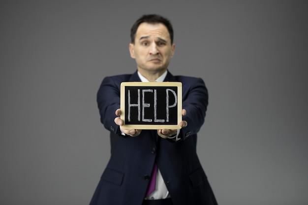 Dueño de negocio preocupado con ayuda firmar en las manos pidiendo apoyo debido a la crisis