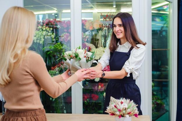 El dueño de la tienda de flores vende un ramo de rosas blancas a un comprador