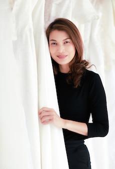 Dueño de la tienda de vestidos de novia asiáticos lindo sentado entre hermoso vestido y mirando a la cámara con feliz.