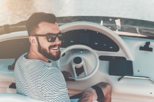 Dueño de yate feliz. sonriente joven sosteniendo la mano en el volante mientras conduce un yate