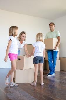 Dueños de casas nuevas felices con dos niños sosteniendo cajas de cartón y corriendo hacia la nueva casa