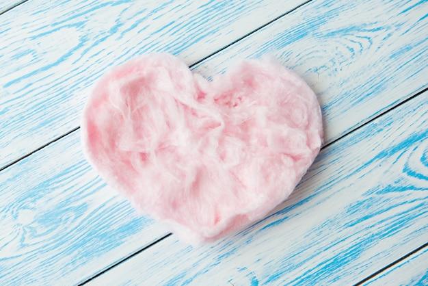 Dulce algodón de azúcar en forma de corazón sobre madera azul