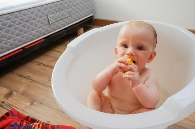 Dulce bebé mojado mordiendo pato de juguete de goma amarillo mientras tiene bañera en casa. fotografía de cerca. concepto de cuidado infantil o salud