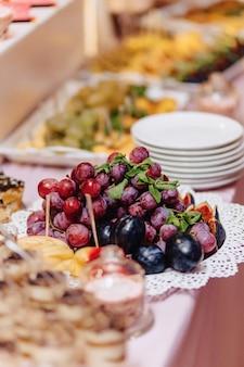 Dulce buffet festivo, fruta, tapas, macarrones y muchos dulces.